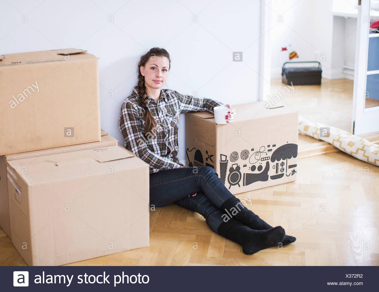 In voller Länge Portrait von junge Frau Kaffeetrinken im neuen Zuhause Stockbild
