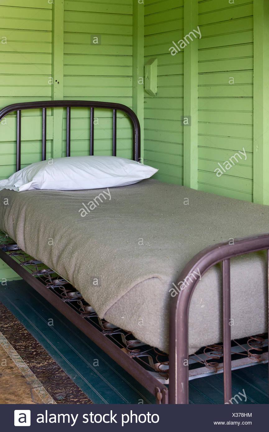 Einfaches Bett im Zimmer. Stockbild