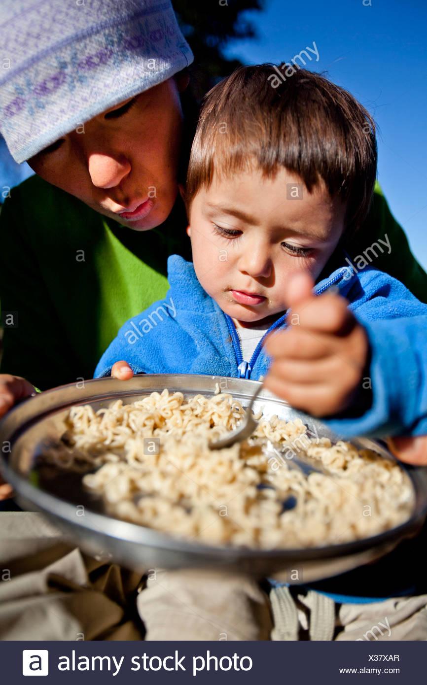 ein Junge sitzt auf seinem Schoß Mütter während sie Nudeln im Hinterland Essen. Sie sind am Squaw Pass lagerten. Stockbild