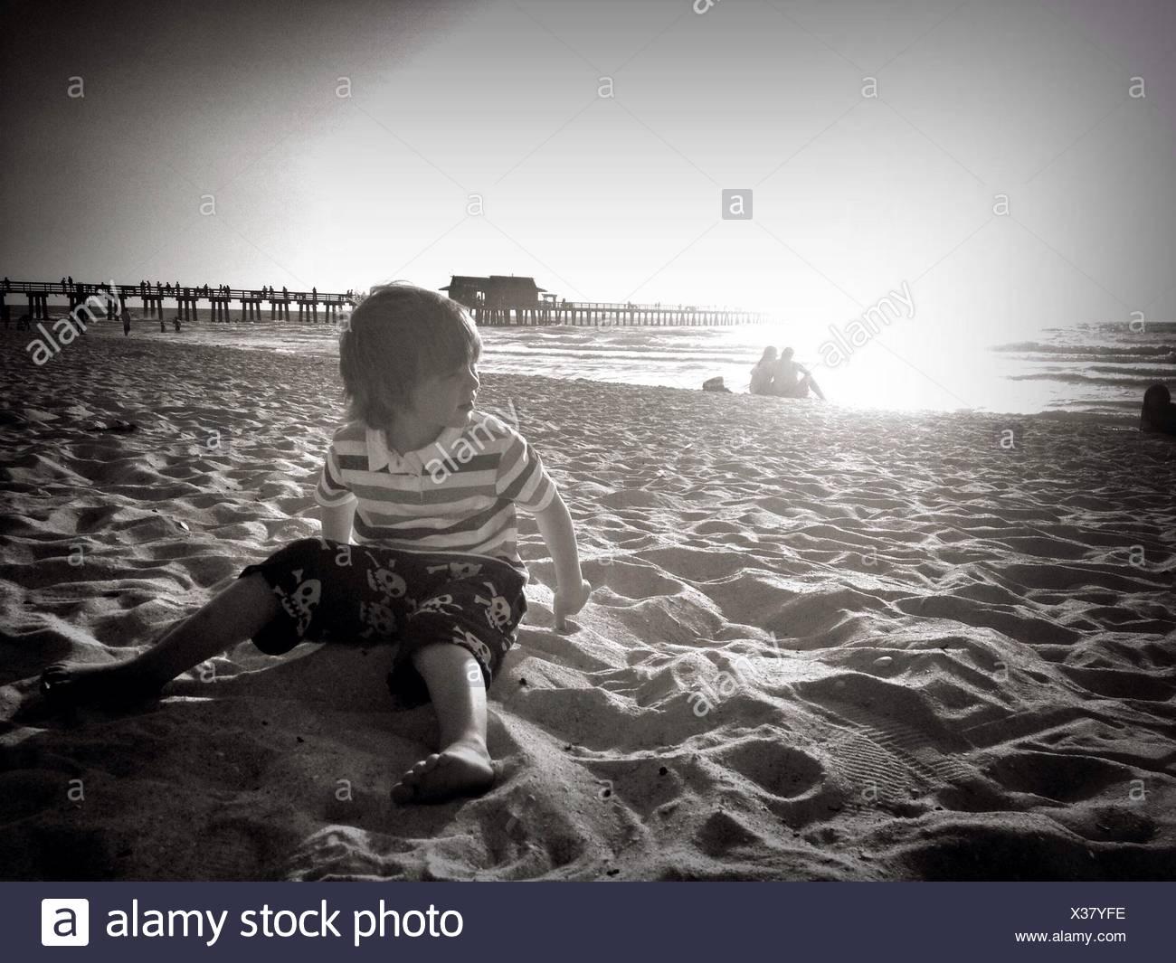 Junge sitzt am Strand Stockbild