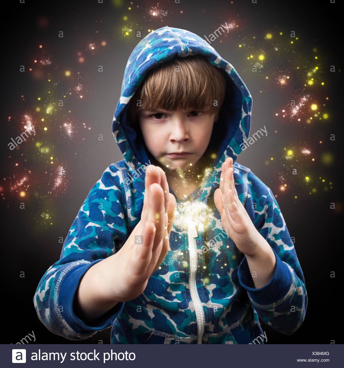 Porträt der junge Zauberer mit funkelt vor grauem Hintergrund Stockbild
