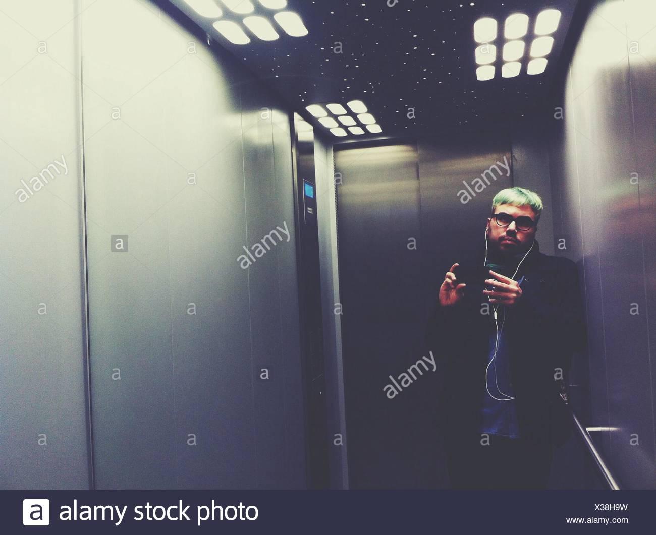 Junger Mann anhören von MP3-Player im Aufzug Stockbild
