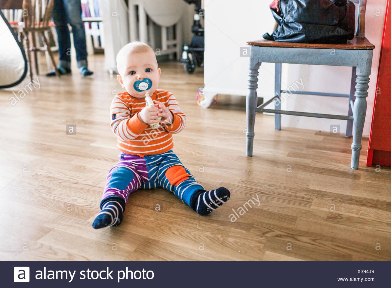 Porträt von Baby mit Schnuller im Mund sitzen auf Parkett zu Hause Stockbild