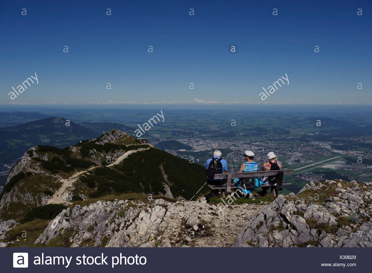 Seniorinnen und Senioren auf einer Bank sitzend genießen die Aussicht vom Salzburger Hochthron Berg, Untersberg, Geiereck und Hochalm Stockbild