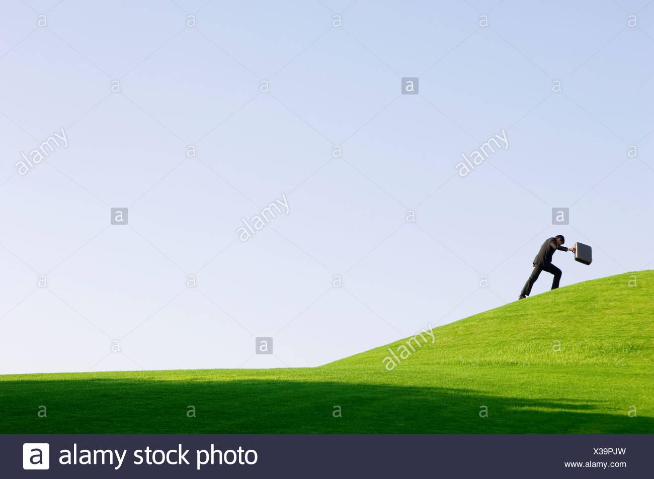 Ein Geschäftsmann mit einem Koffer zu Fuß bergauf Stockbild