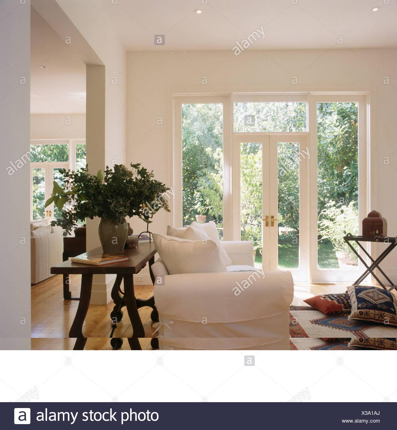 Große Vase mit Blumen auf antiker Tisch hinter weißen Sofa im ...