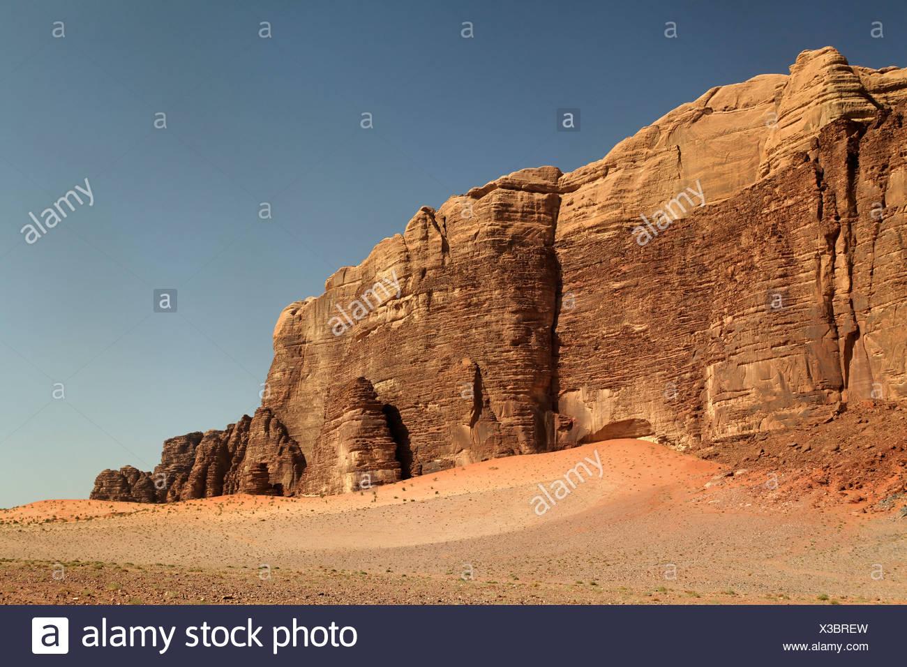 Wüste Ebene mit einem steigenden Bergmassiv, Wadi Rum, Haschemitischen Königreich Jordanien, Naher Osten, Asien Stockbild