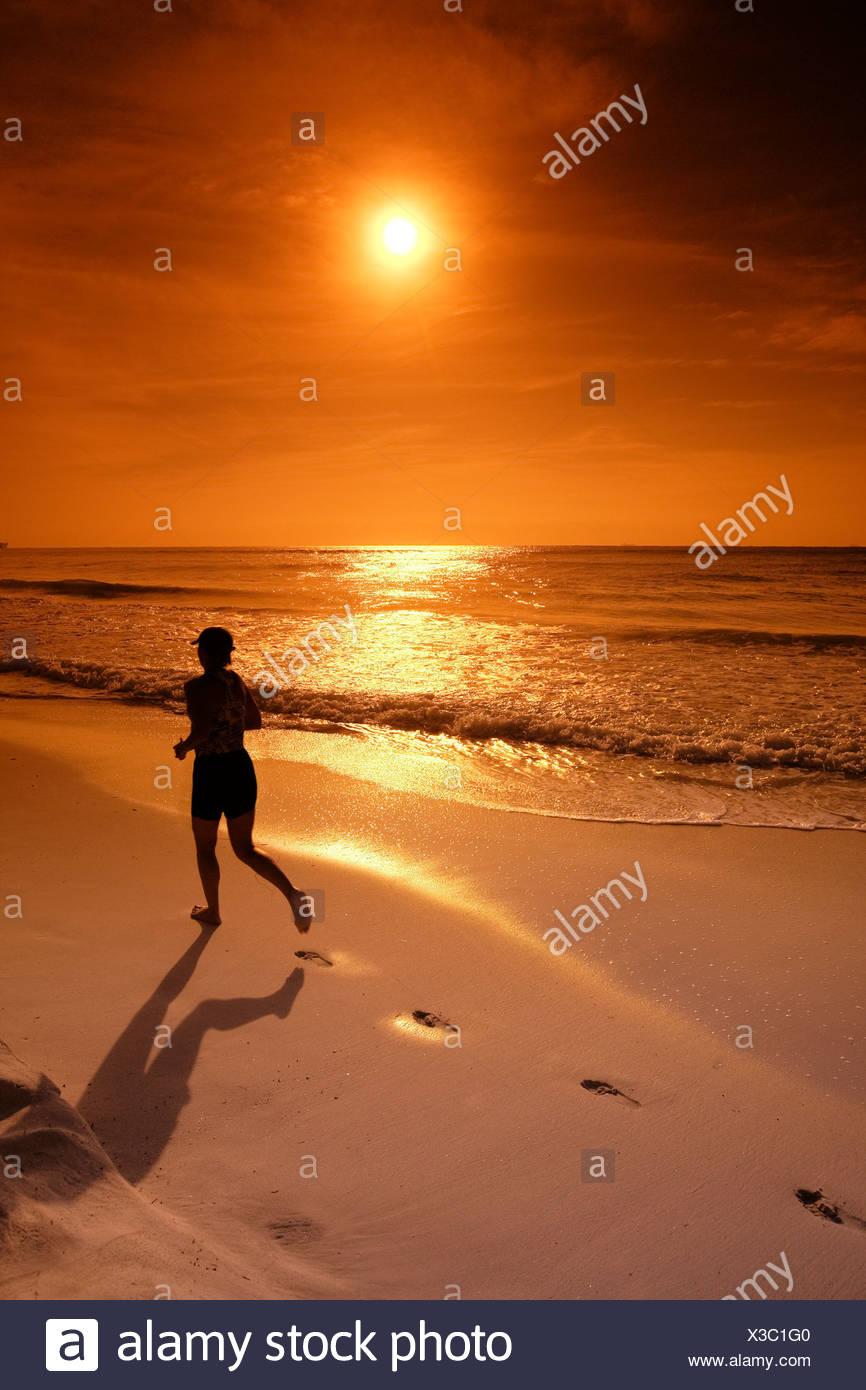 Silhouette des weiblichen Jogger entlang des Ozeans Stockbild