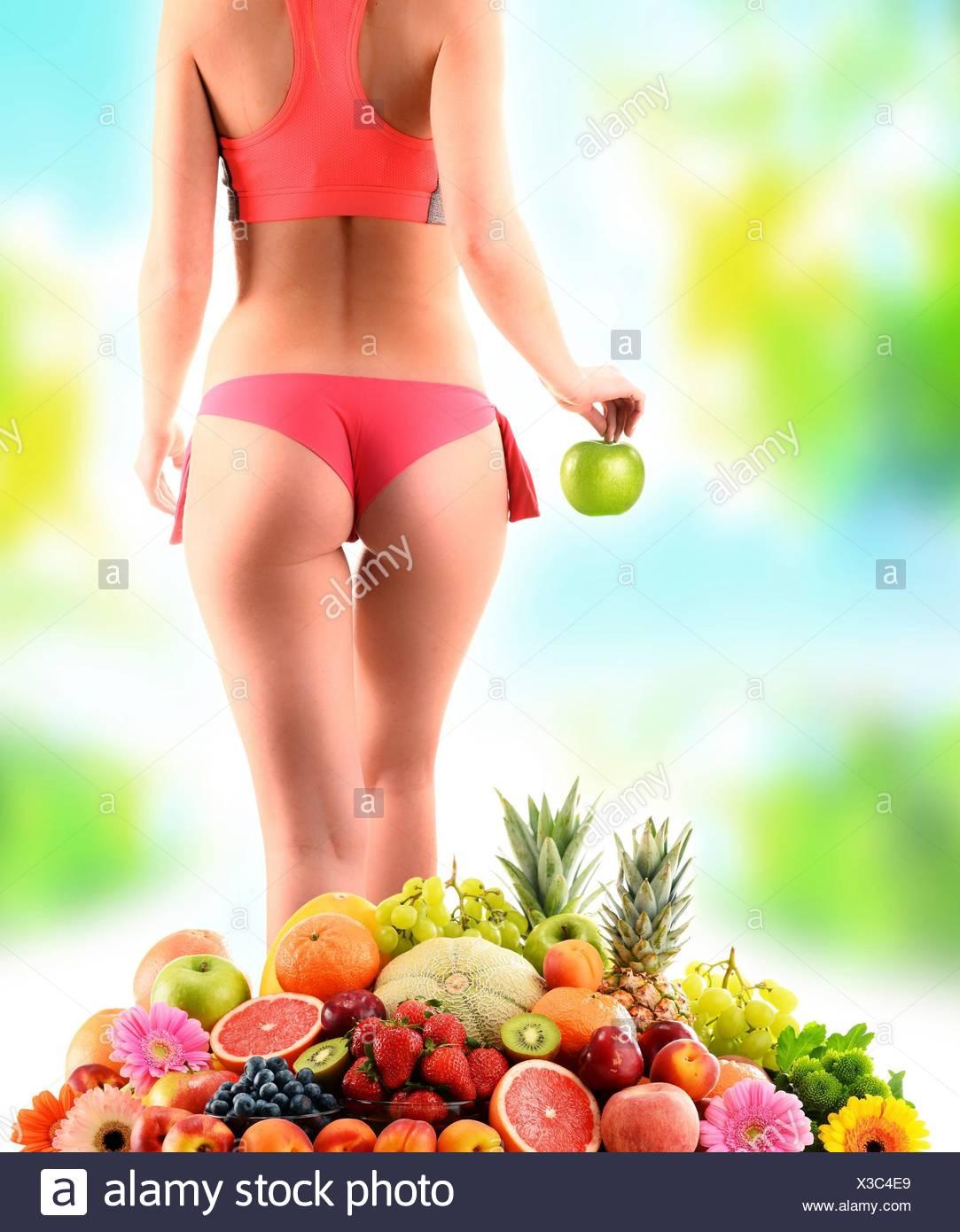Gewicht-Verlust. Schlanke Frau hält einen Apfel und Zusammensetzung mit frischem Obst. Stockbild