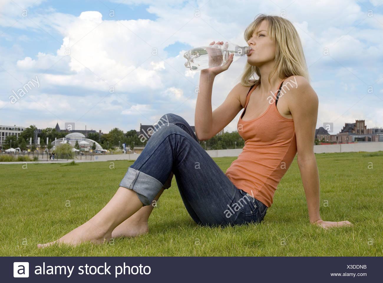 Sitzt Frau Wiese Mineralwasser Getränke seitwärts Serie Menschen ...