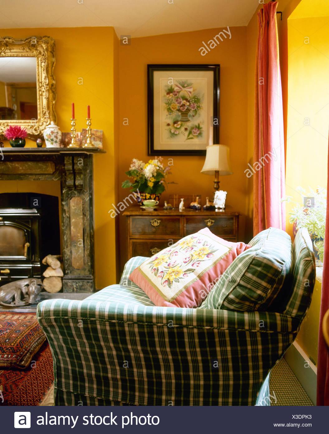 Grün überprüft Sofa mit rosa Blumen Kissen in blass orange ...