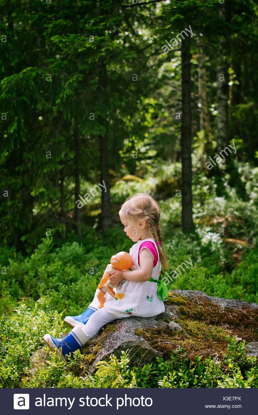 Finnland, Paijat-Hame, Seitenansicht der Mädchen (2-3) mit Puppe auf Felsen sitzend Stockbild