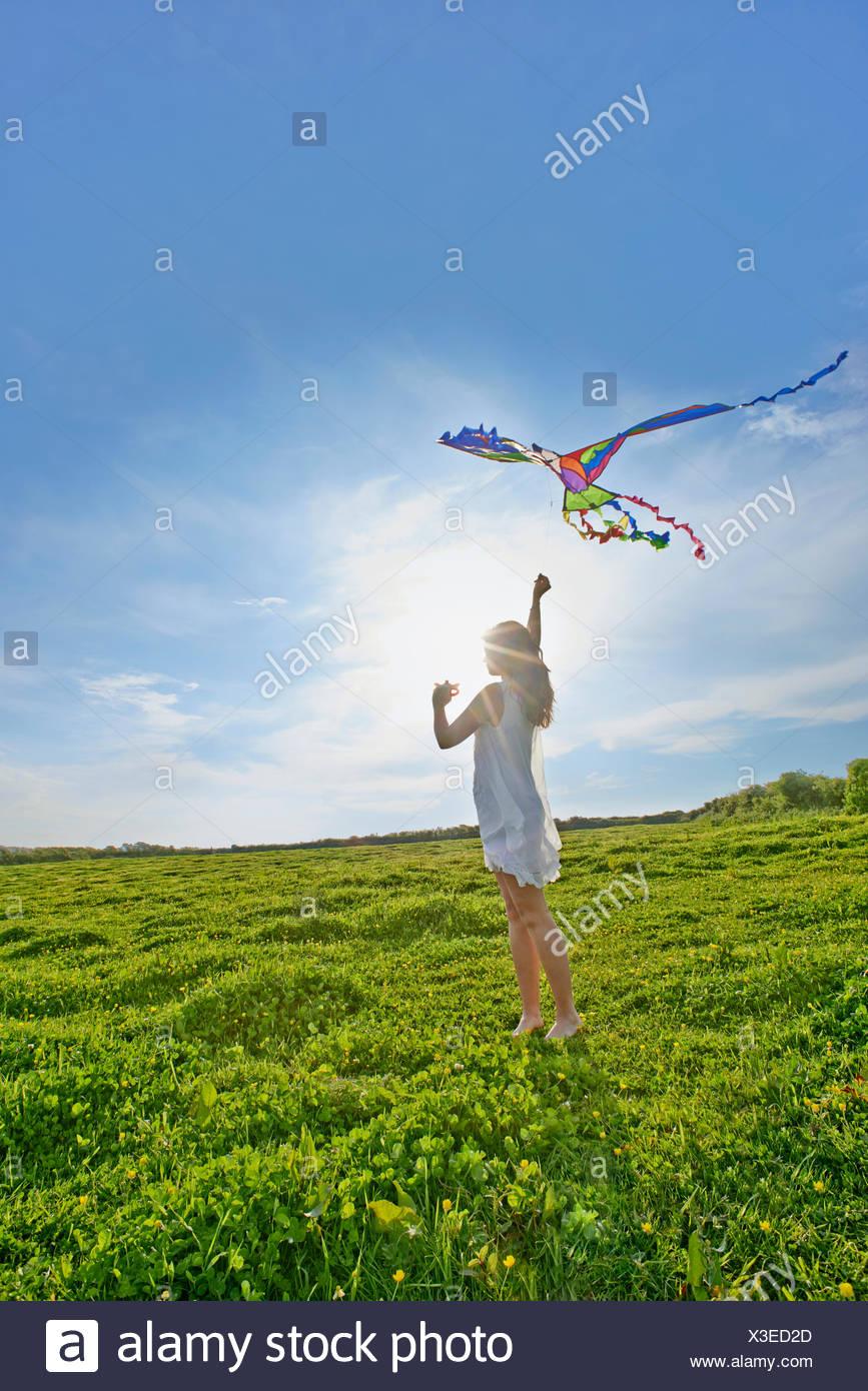 Junge Frau, die einen Drachen im Feld Stockbild