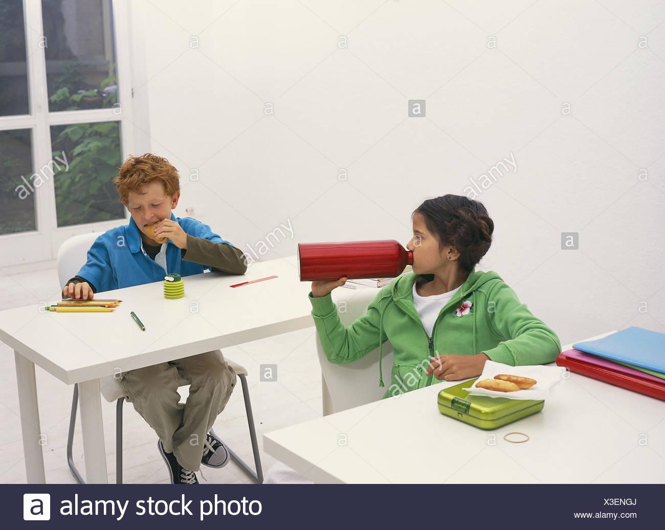 Klassenzimmer, Pause, Schuljunge, Essen, trinken, Schule, Schulbänke, Schulferien, Unterricht, Pause, Person, Kinder, zwei, junge, Mädchen, Schülerinnen und Schüler, Grundschulkinder, Schule, Freunde, Freunde, Hunger, Durst, Trinkflasche, Pause-Brot, Notizbücher, Stifte, Sit, Zeit leben, Schulzeit, Schulpflicht, innen, Stockbild