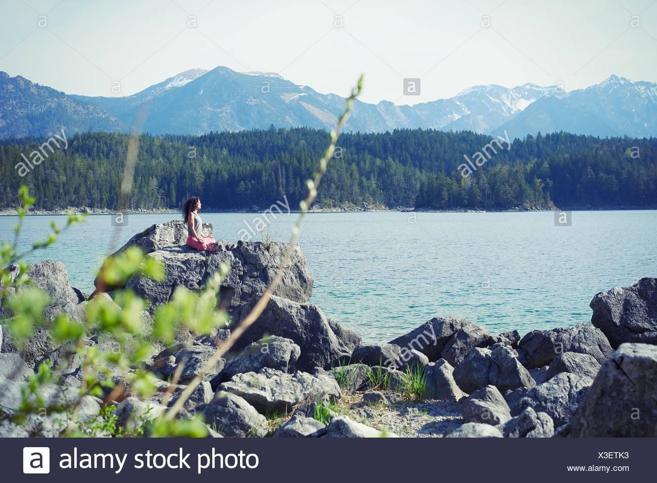 Mitte Erwachsene Frau, sitzt auf Felsen in Yogaposition Stockbild