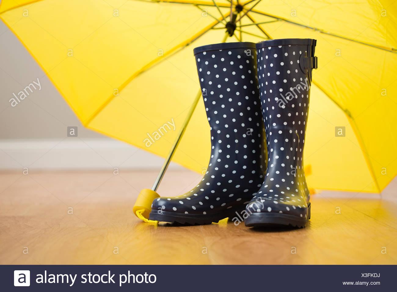Polka Dot Gummistiefel unter gelben Regenschirm Stockbild