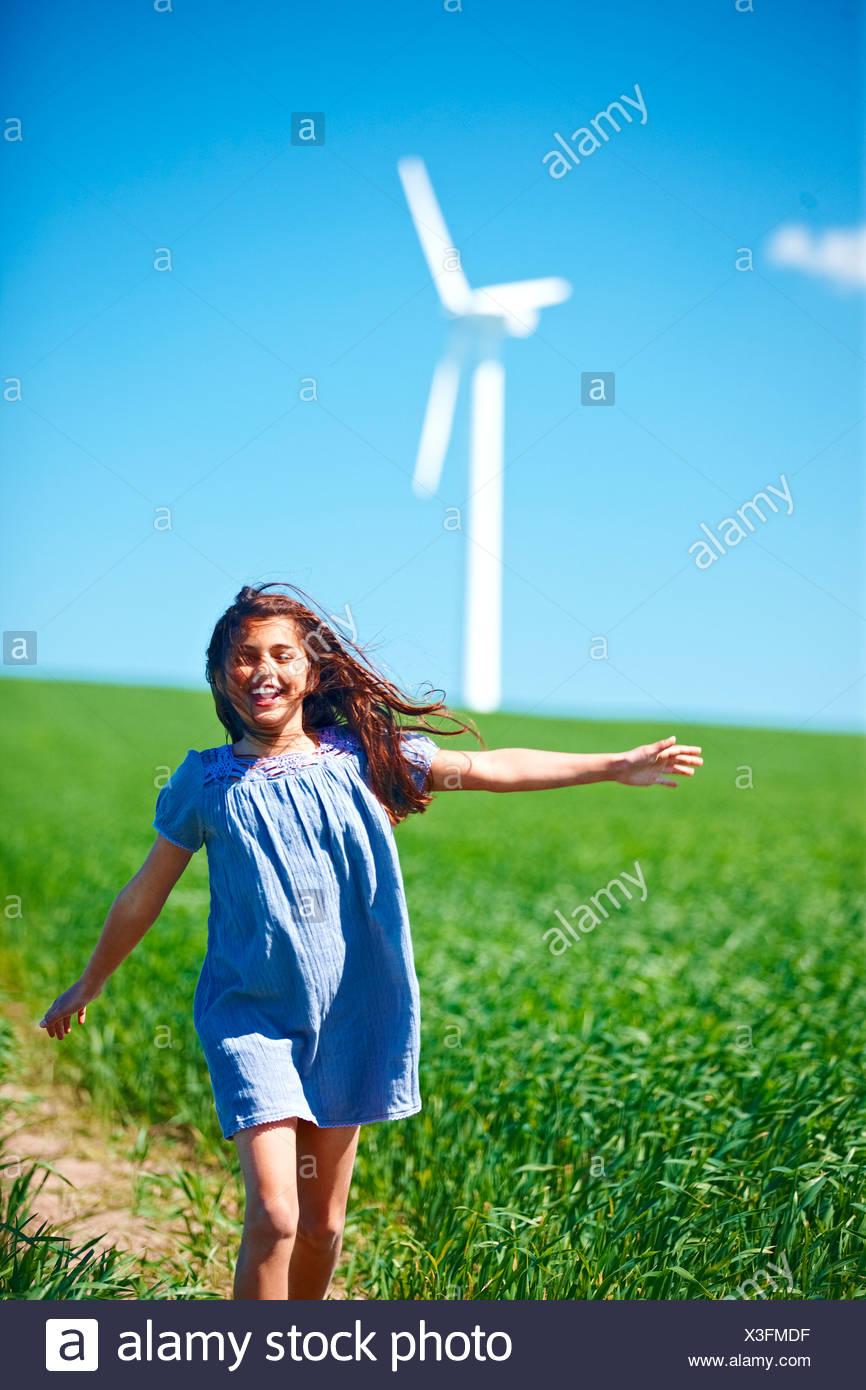 Mädchen im Feld mit Windkraftanlage Stockbild