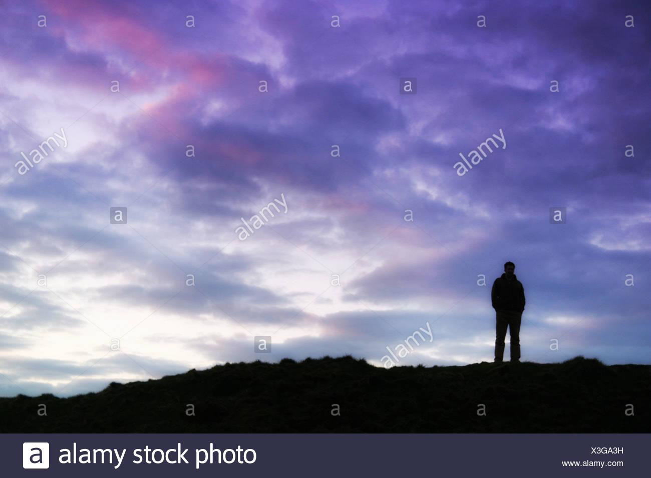 Mann stand auf einem Hügel bei Sonnenuntergang Stockbild