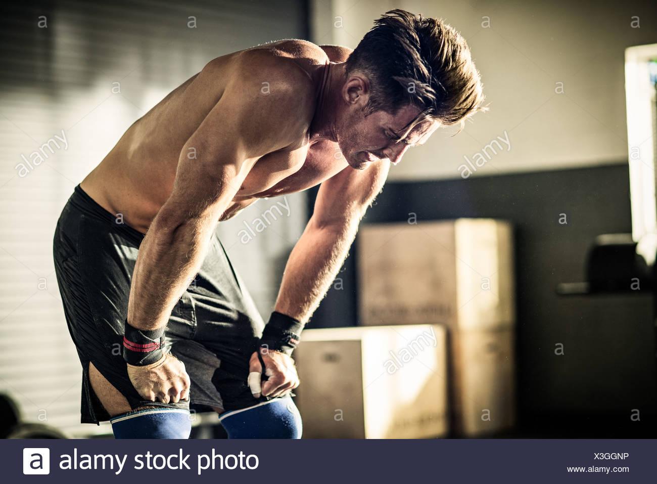 Junger Mann nach vorne beugen mit Erschöpfung im gymnasium Stockbild