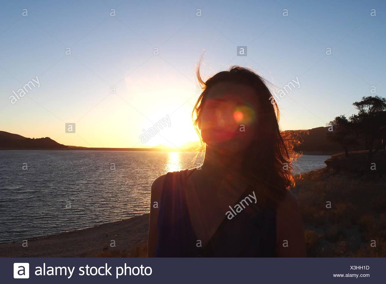 Sonnenlicht fällt auf Gesicht der Frau stehen am Strand Stockbild