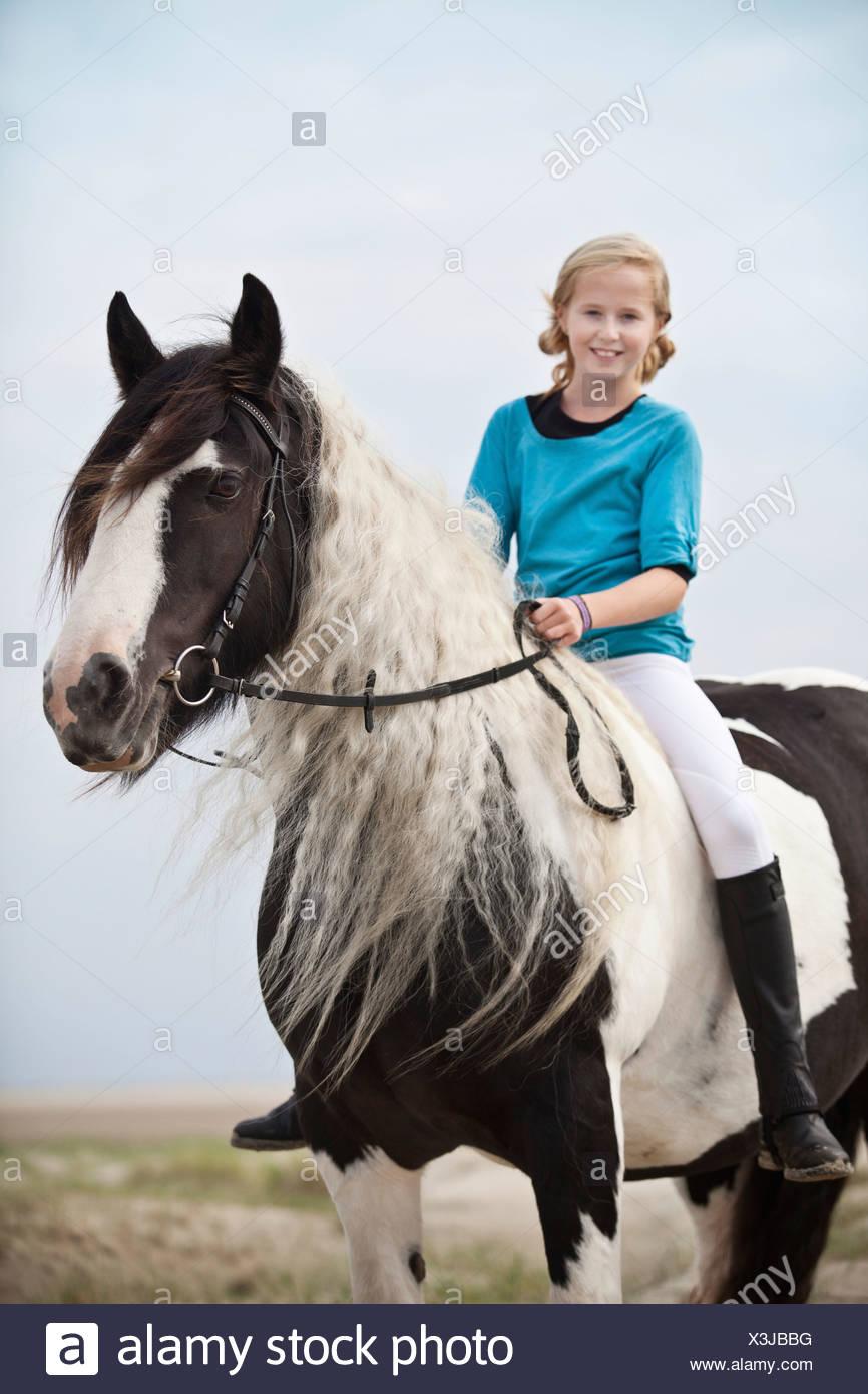 Junge Horserider Reiten ohne Sattel auf eine Stute, Pony, Tinker, schwarz und weiß kariert in den Dünen am Strand, Borkum Stockbild