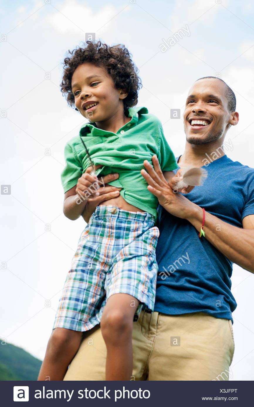 Ein Mann hob seinen Sohn in den Armen, spielen im Freien. Stockbild