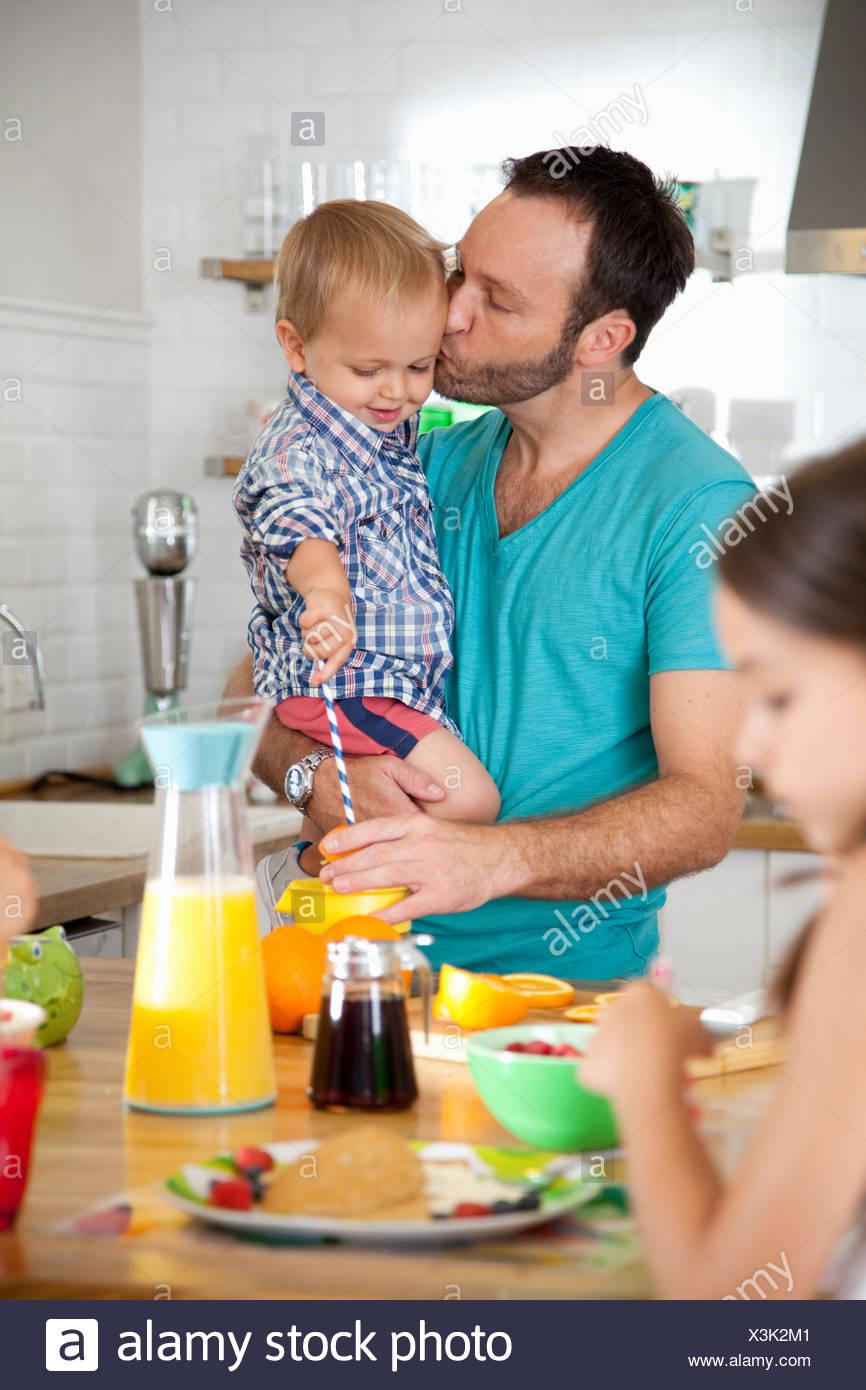 Mitte erwachsener Mann-Multitasking-Frühstück mit Sohn und Tochter Stockbild