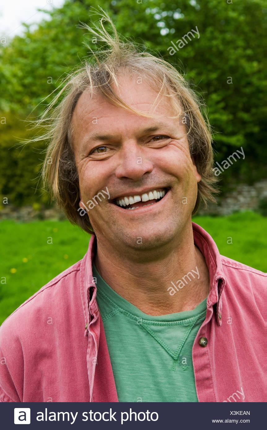 Ein Mann in Freizeitkleidung mit blonden Haaren, lächelt breit. Stockbild