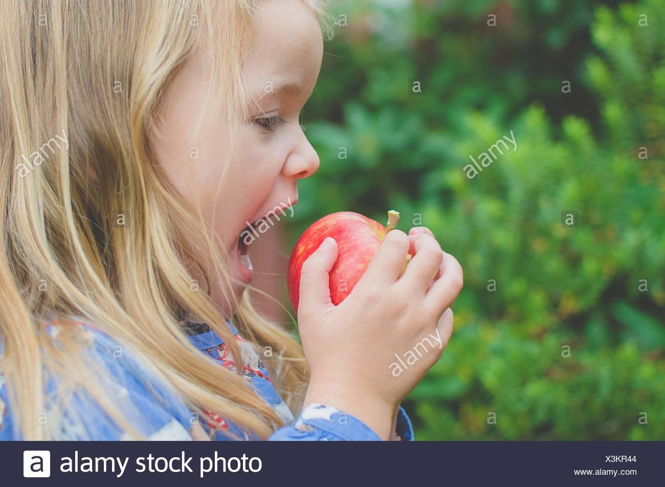 Seitenansicht eines Mädchens zu nehmen einen Schluck aus einem Apfel Stockbild