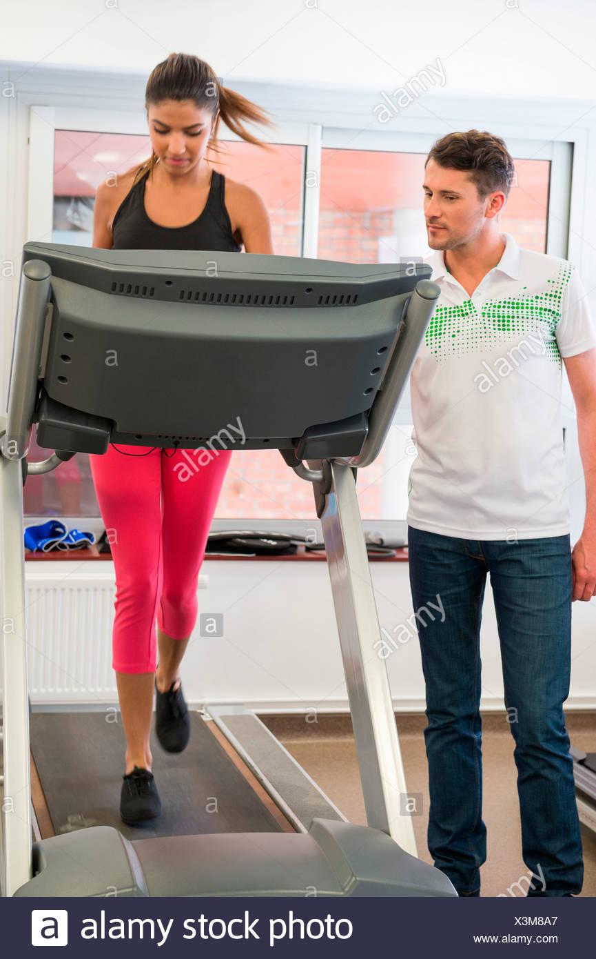 Lehrer unterrichten eine Frau auf einem Laufband im Fitnessstudio Stockbild