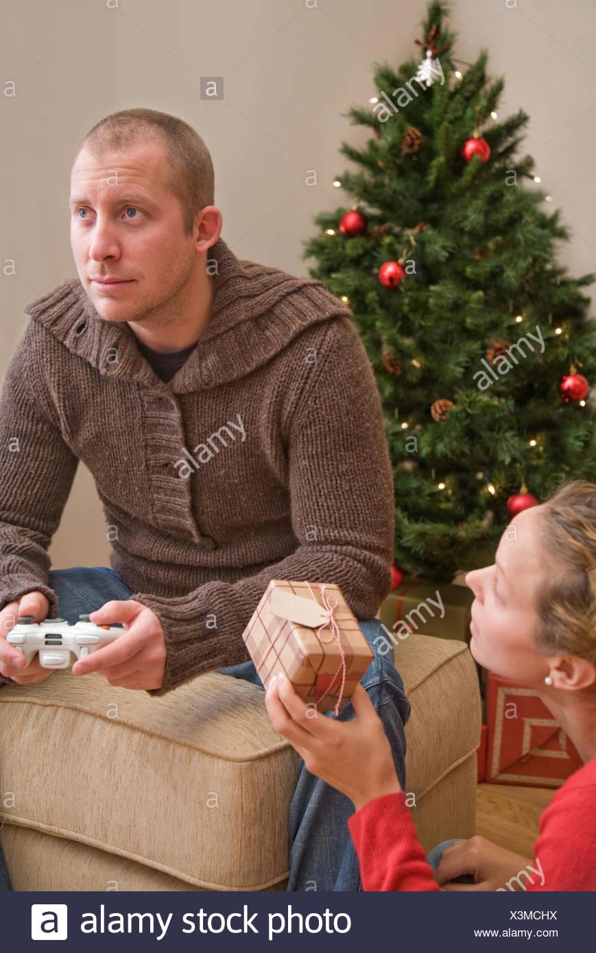 Frau, ein Mann mit Computerspielen Weihnachtsgeschenk geben ...