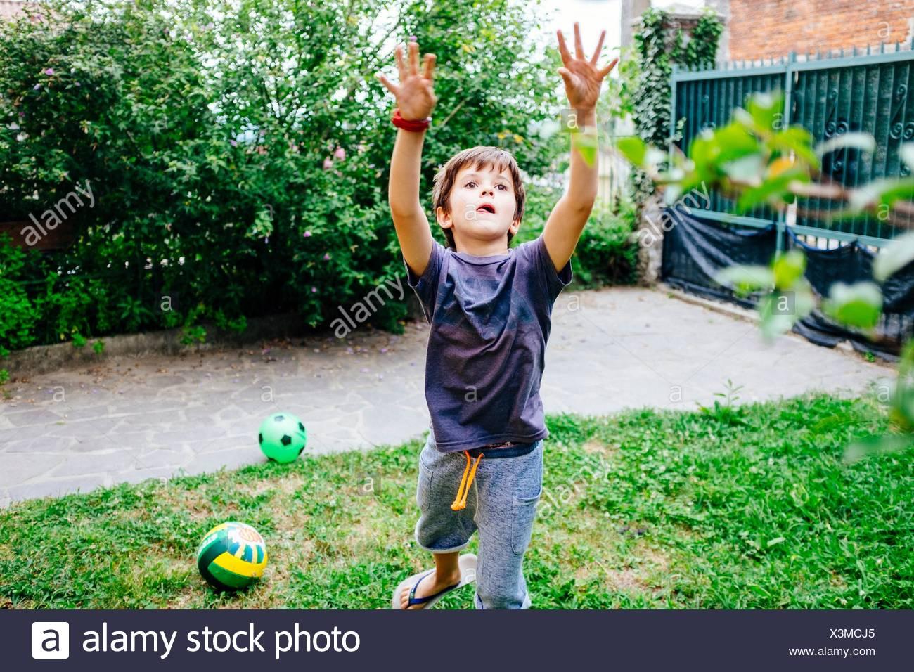 Kind spielt Ball in den Garten des Hauses Stockbild