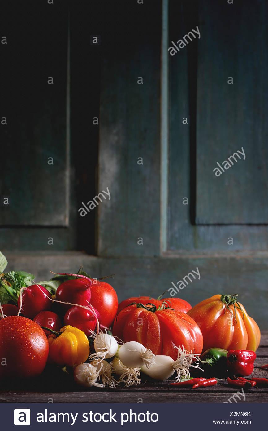 Haufen frische reife buntem Gemüse Tomaten, Chilischoten, Frühlingszwiebeln und Haufen von Rettich über alten Holztisch. Dunklen Rost Stockbild