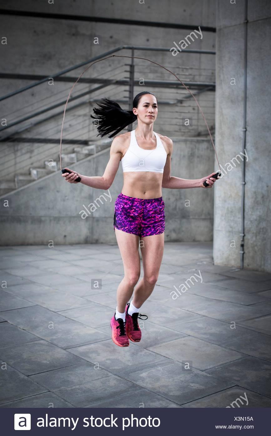 -MODELL VERÖFFENTLICHT. Junge Frau mit einem Seil springen. Stockbild