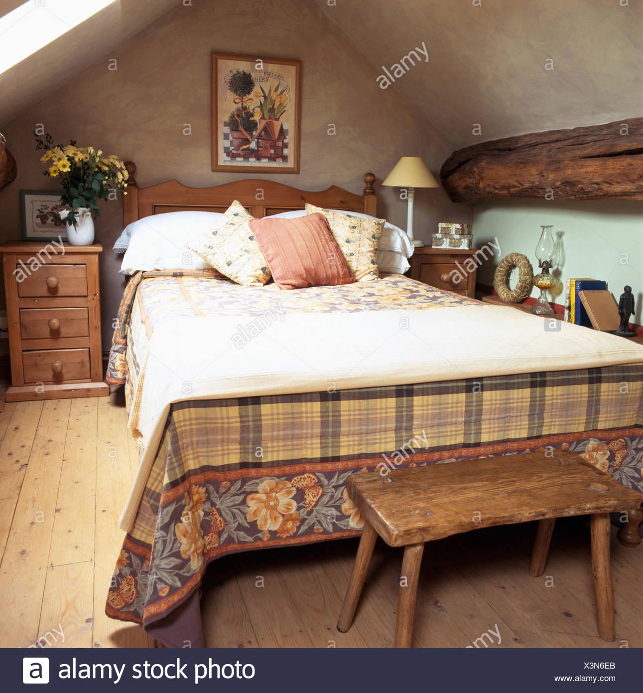 Alte hölzerne Hocker unter Bett mit Creme Wurf und gemusterten ...