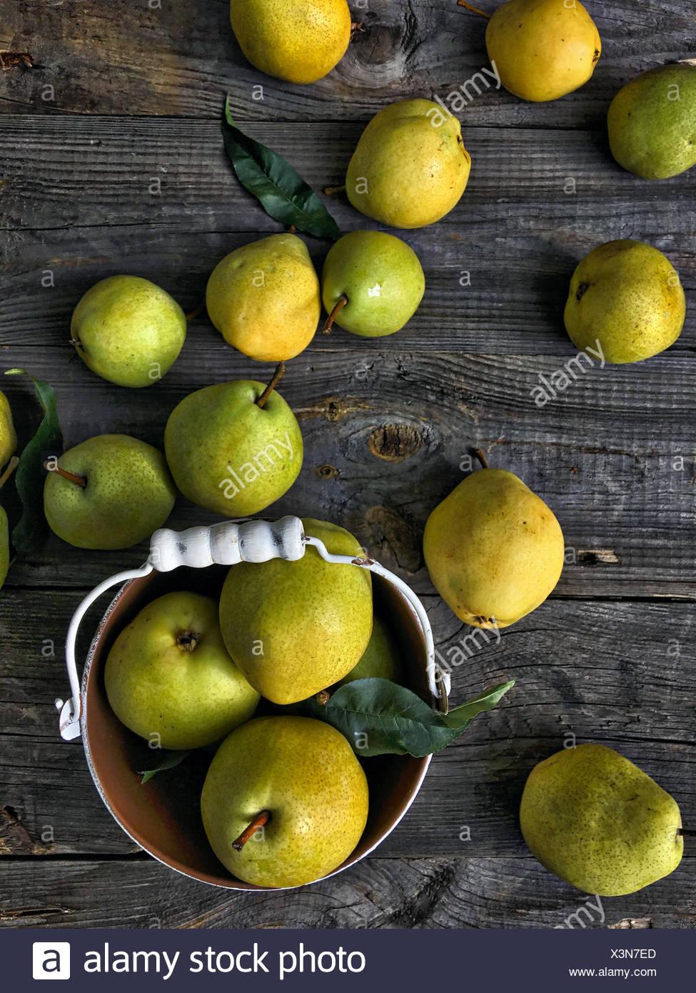 Reife, gelbe und grüne Birnen auf einem Tisch Stockbild