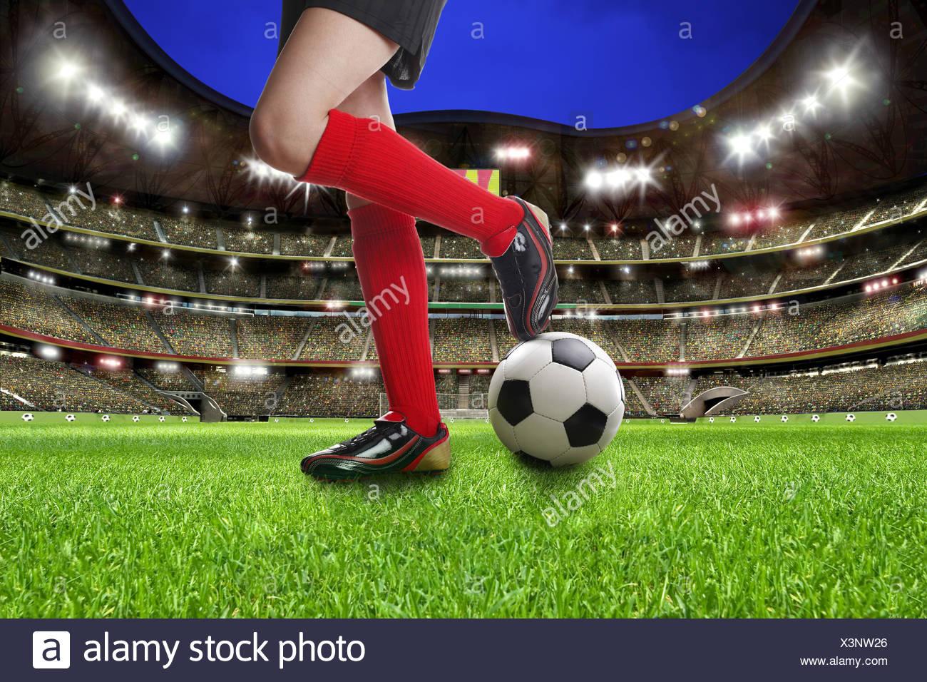 Beine der weiblichen Fußballer auf einem Fußball im Fußballstadion, Abbildung Stockfoto