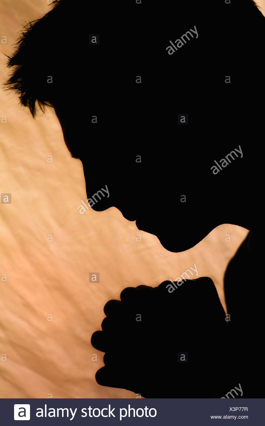 Silhouette der Mann, der betet Stockbild