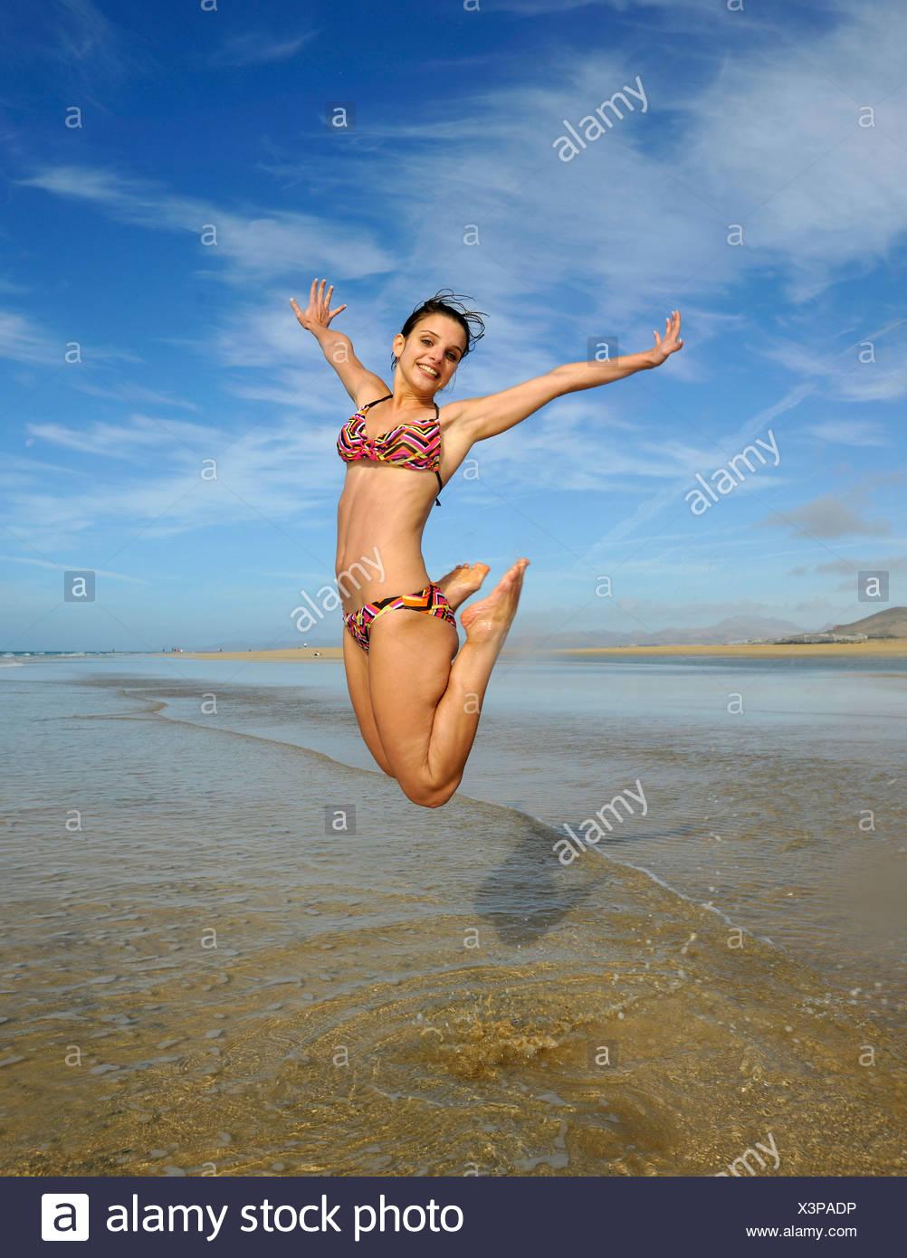 Springen Sie in die Luft, junge Frau am Meer, symbolisches Bild für Vitalität, Lebensfreude, Strand Playa de Sotavento de Jandia Stockbild