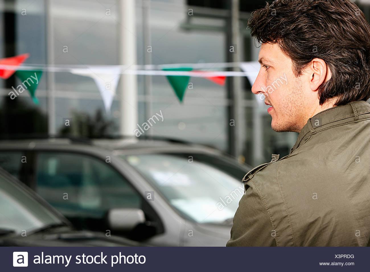 Seitenansicht des Mannes betrachtet man Autos bei Autohändler Stockbild
