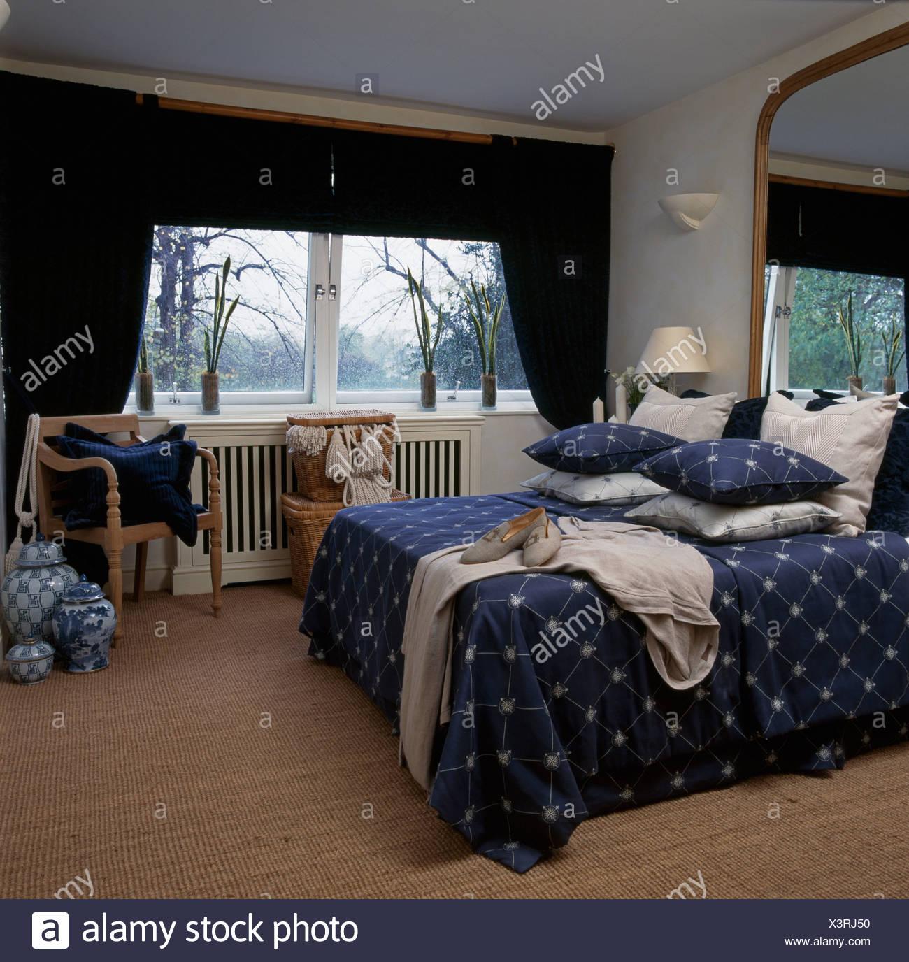 Gestapelt Auf Bett Mit Kissen Blau Stern Gemusterten Bettdecke Im Schlafzimmer Mit Sisal Teppich Und Dunkle Blaue Vorhange Stockfotografie Alamy