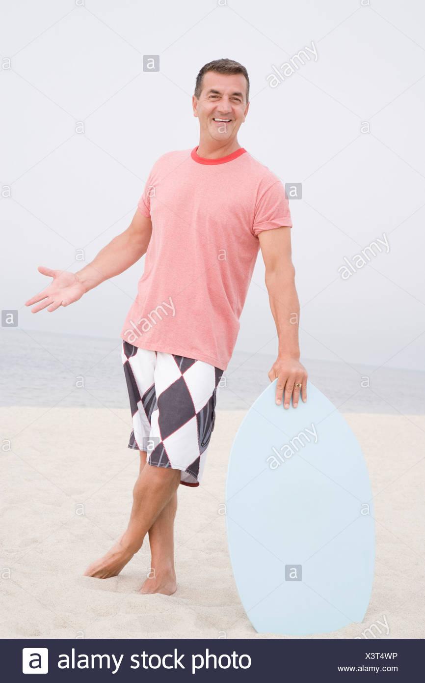 Reifer Mann hält ein Bodyboard am Strand Stockbild