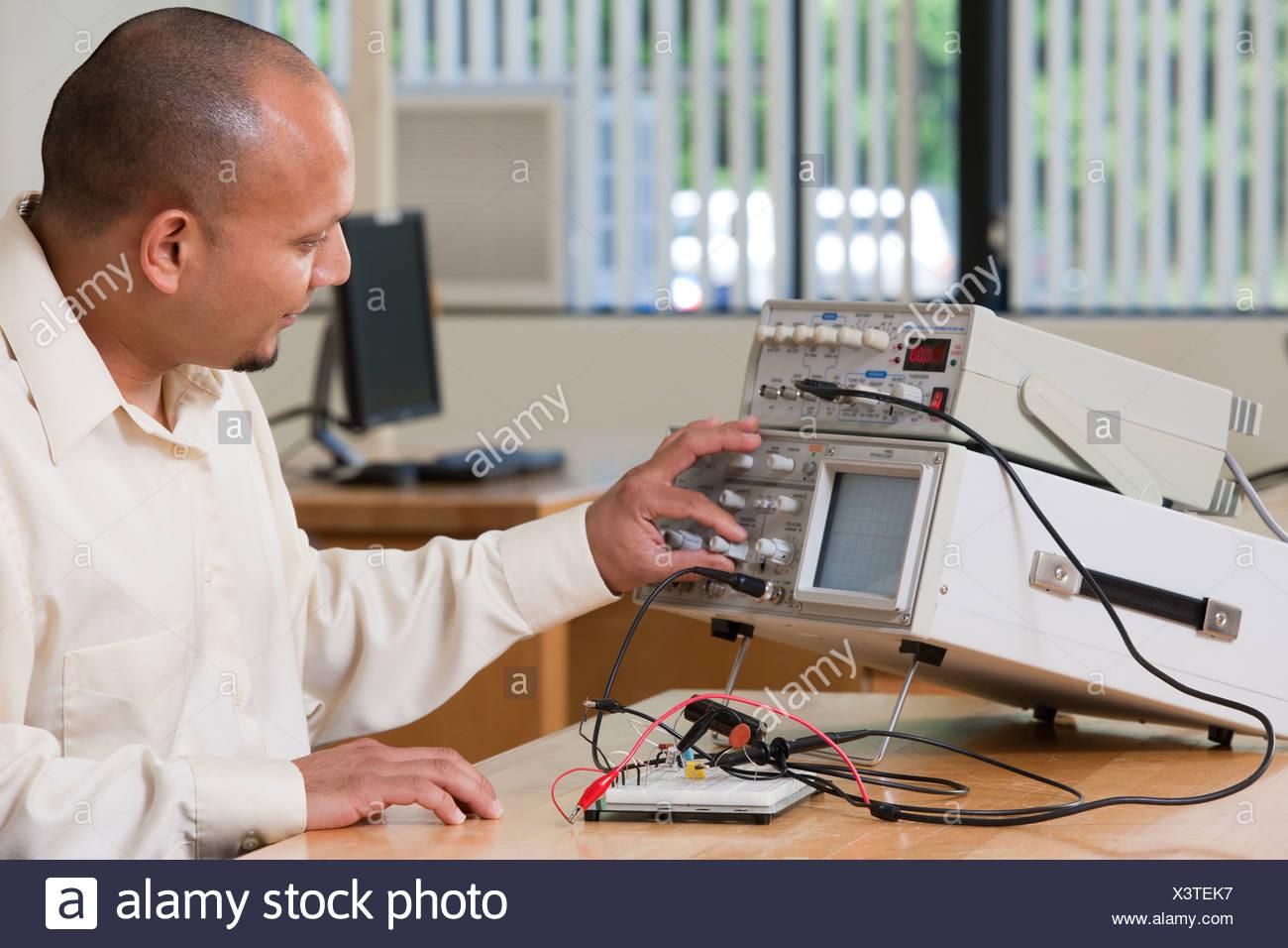 Hispanische Ingenieurstudent Anpassung der Signalpegel am Oszilloskop und Funktion Generator in einem Klassenzimmer Stockbild