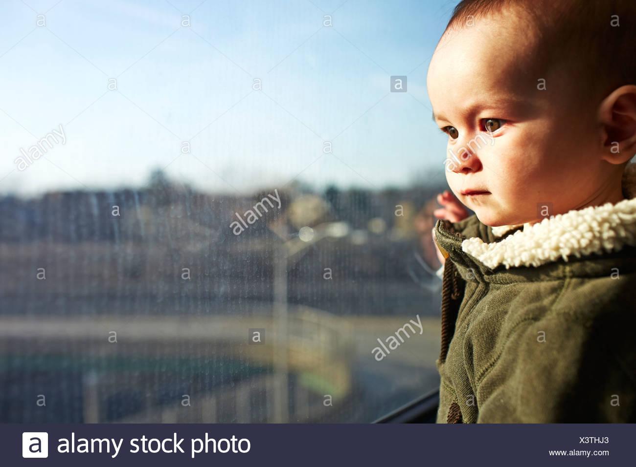 Nahaufnahme von Baby junge starrte aus dem Fenster Stockbild