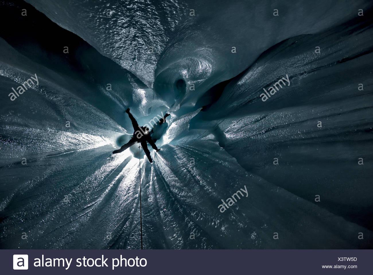 Suchen Sie gerade nach unten eines der vielen vertikale Schächte und Gruben in einem Moulin auf Aletschgletschers. Italienischer Höhlenforscher Alessio Romeo hängt ein Stockbild