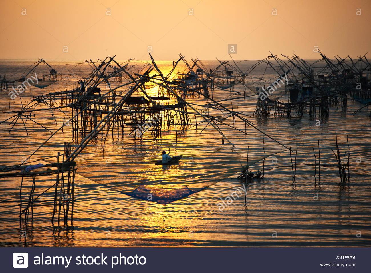 Thailand, Phatthalung, Chinesische Fischernetze bei Sonnenaufgang im Meer Fischschwärme installiert Stockfoto