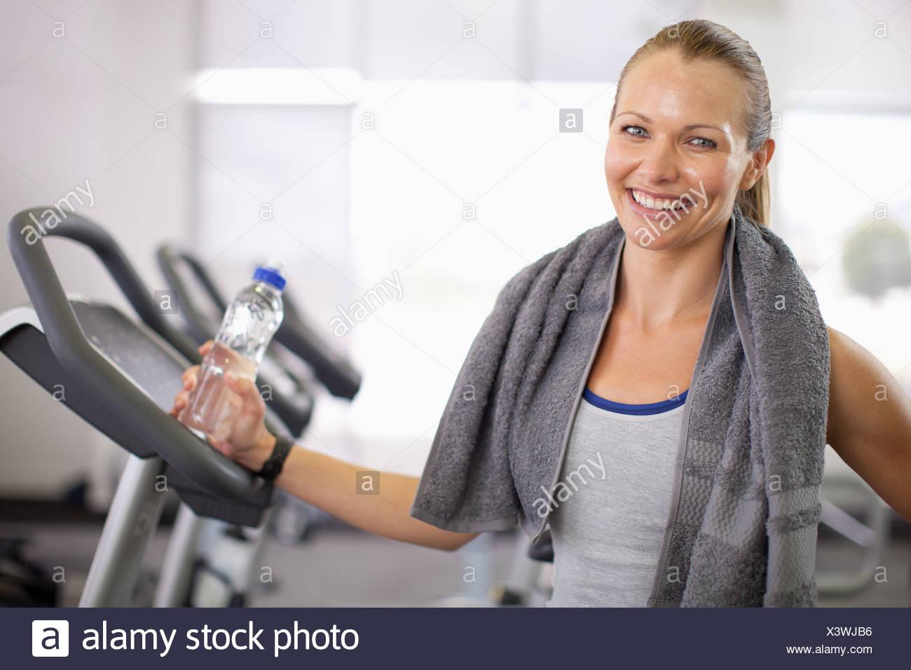 Frau mit Mineralwasser im Fitness-Studio Stockbild