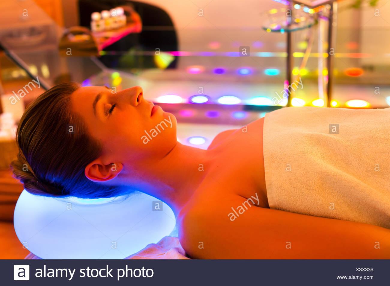 Frau mit einer Behandlung im Spa mit Farbtherapie Stockbild