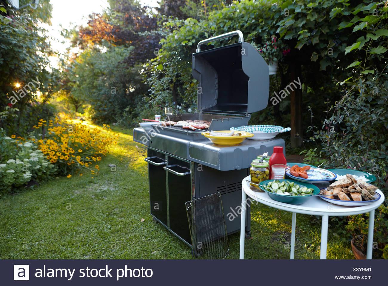 grillplatz mit großem grill, salate und beilagen in den garten am