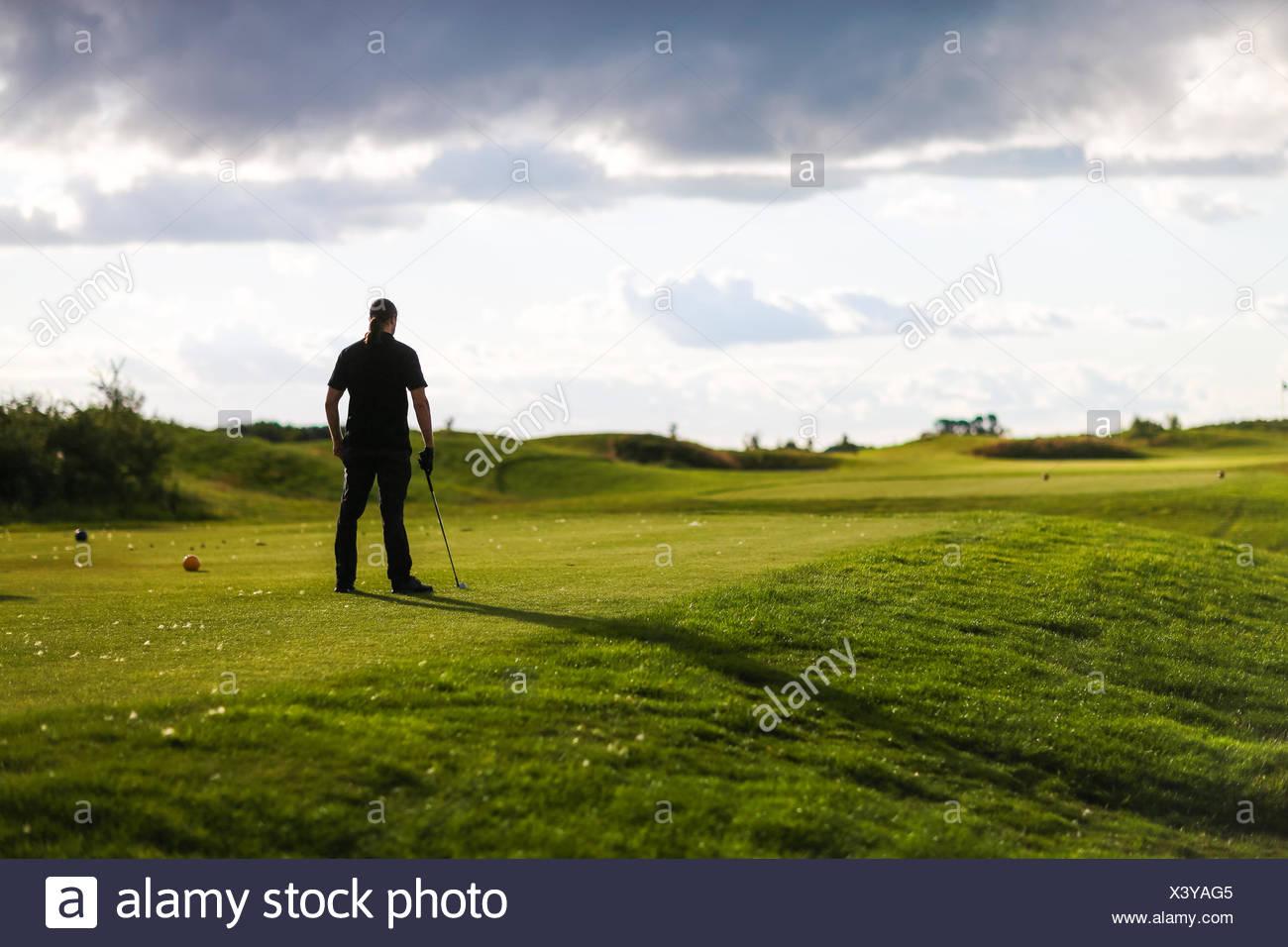 Mann mit Golf Club blickt auf stürmischen Golfplatz Stockbild